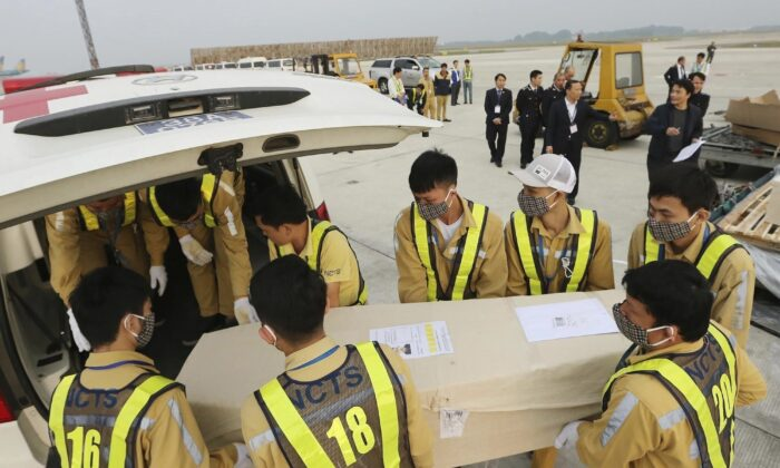 Airport personnel load a coffin into an ambulance at the Noi Bai airport on Nov. 27, 2019 in Hanoi, Vietnam. (Vietnam News Agency via AP)