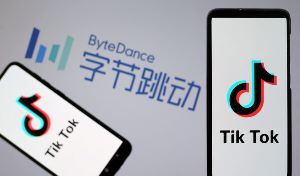 TikTok logos are seen on smartphones in front of displayed ByteDance logo in this illustration