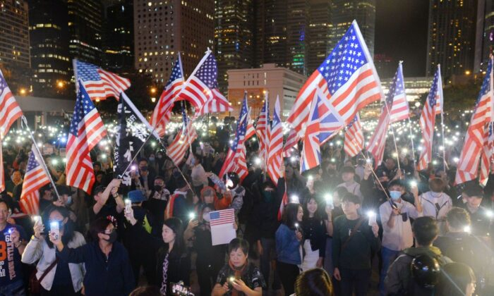 Protestors wave U.S. flags and hold up their lit-up mobile phones as they attend a gathering at the Edinburgh place in Hong Kong on Nov. 28, 2019. (Sung Pi Lung/The Epoch Times)