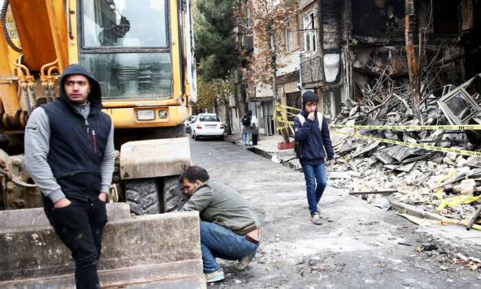 People walk near a burnt bank, after protests against increased fuel prices, in Tehran, Iran Nov. 20, 2019. (Nazanin Tabatabaee/WANA (West Asia News Agency) via Reuters)