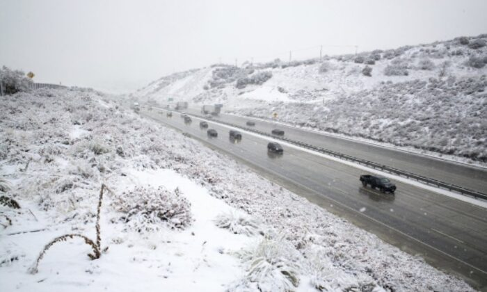 Snow falls along the Interstate 5 freeway at the Tejon Pass as travelers try to get in and out of Southern California for the Thanksgiving holiday, on Nov. 27, 2019, near Gorman, Calif.. (David Crane/The Orange County Register via AP)