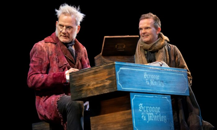 """Ebenezer Scrooge (Campbell Scott) and his bookkeeper, Bob Cratchit (Dashiell Eaves) as they appear in Jack Thorne's stage adaptation of """"A Christmas Carol."""" (Joan Marcus)"""