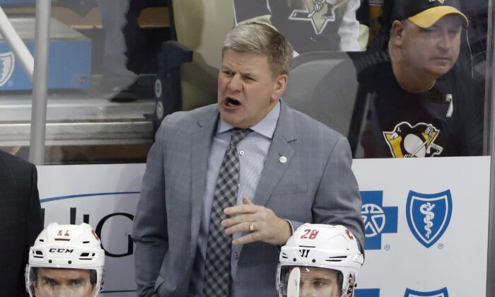 Calgary Flames head coach Bill Peters gives instructions during the first period of an NHL hockey game against the Pittsburgh Penguins in Pittsburgh on Feb. 16, 2019. The Flames won 5-4. (AP Photo/Gene J. Puskar)