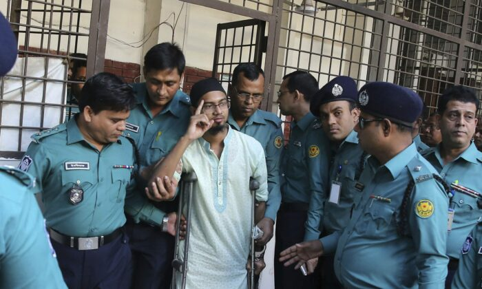 Police escort a member of a banned militant group after he was sentenced to death for an attack on a Dhaka cafe that killed more than 20 people in Dhaka, Bangladesh, on Nov. 27, 2019. (Mahmud Hossain Opu/AP Photo)