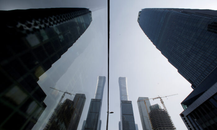 Skyscrapers in the Central Business District (CBD) are reflected in a window in Beijing, China on March 4, 2019. (Thomas Peter/Reuters)