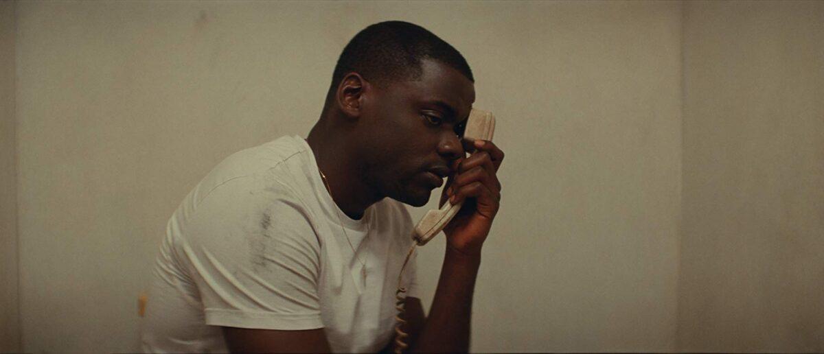 black man in white t-shirt on phone