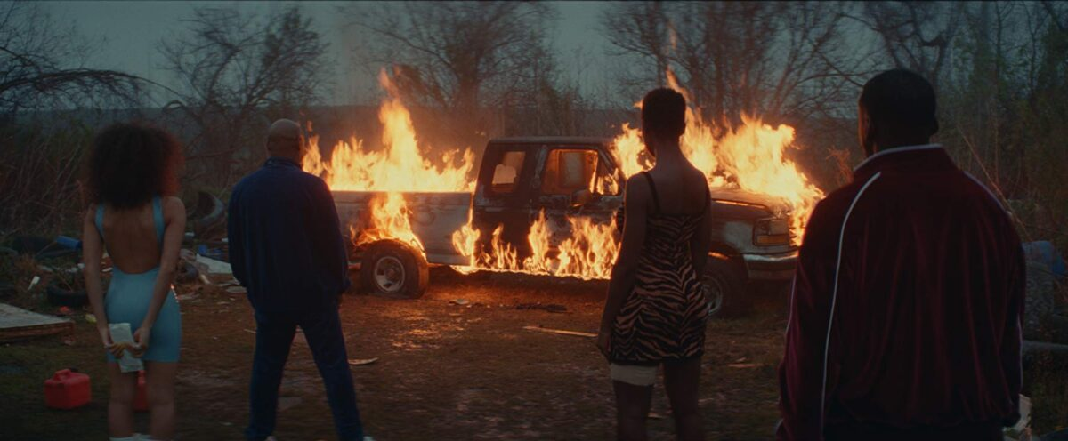 two men and two women watch burning truck
