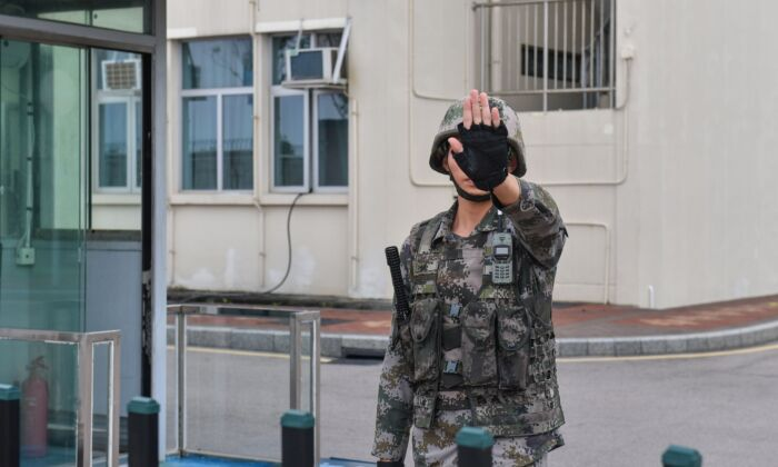A Chinese soldier gestures at an entrance to the headquarters of the People's Liberation Army Hong Kong Garrison in the Admiralty district in Hong Kong on October 7, 2019. (NICOLAS ASFOURI/AFP via Getty Images)