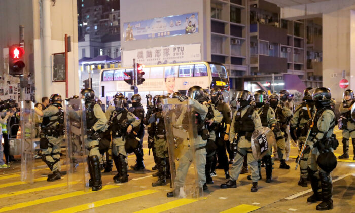Riot police officers block the street as protesters rally outside Prince Edward MTR station in Hong Kong, China, on Nov. 30, 2019. (Marko Djurica/Reuters)