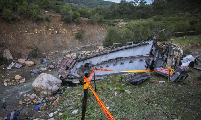 The debris of a regional bus that crashed off a hill in Tunisia on Sunday, Dec.1, 2019. (AP Photo/Riadh Dridi)