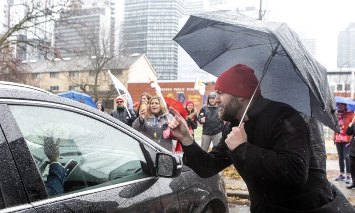 Protesting teachers gather around Ontario Education Minister Stephen Lecce's car as he leaves  after making an announcement at a Toronto school on Nov. 27, 2019. Ontario public school teachers have embarked on job action as a result of a dispute with the provincial government. (The Canadian Press/Chris Young)