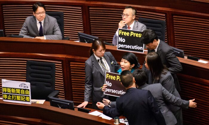 """Hong Kong pro-democracy legislator Claudia Mo (R) is surrounded by security as she shouts """"Free press! No Persecution!"""" as Chief Executive Carrie Lam (not pictured) arrives to deliver her policy address at the Legislative Council (Legco) in Hong Kong on Oct. 10, 2018. (Anthony Wallace/AFP via Getty Images)"""