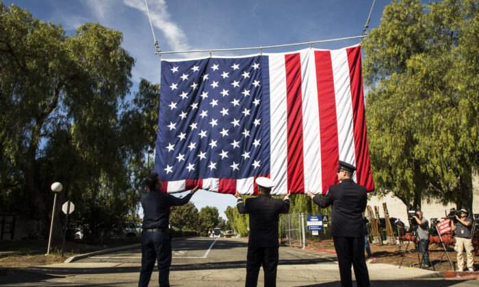 Firefighters help raise an American flag honor of Sgt. Ron Helus at The Calvary Community Church for  memorial service in his honor on November 15, 2018 in Westlake Village, California. Sgt. Helus was killed in a mass shooting at the Borderline Bar and Grill in Thousand Oaks, California on November 7.  Barbara Davidson/Getty Images