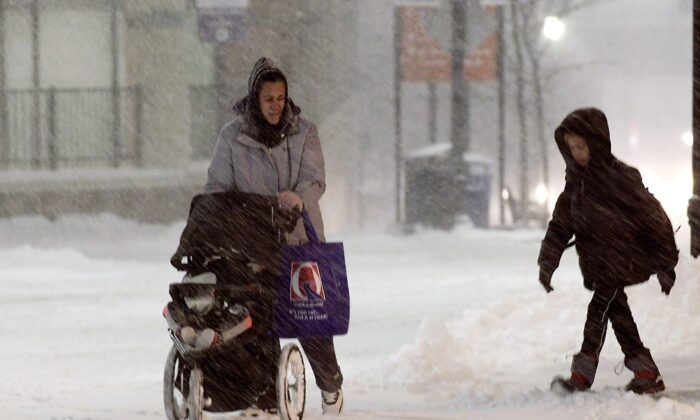 A family walks up Front Street during a snow storm in Worcester, Mass., on Dec. 1, 2019. (Christine Peterson/Worcester Telegram & Gazette via AP)