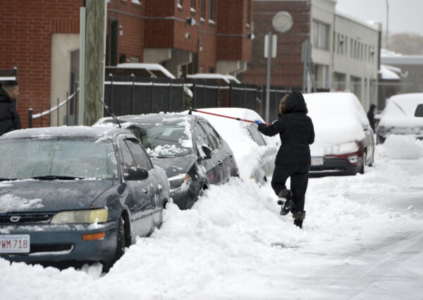 A woman clears snow from a car