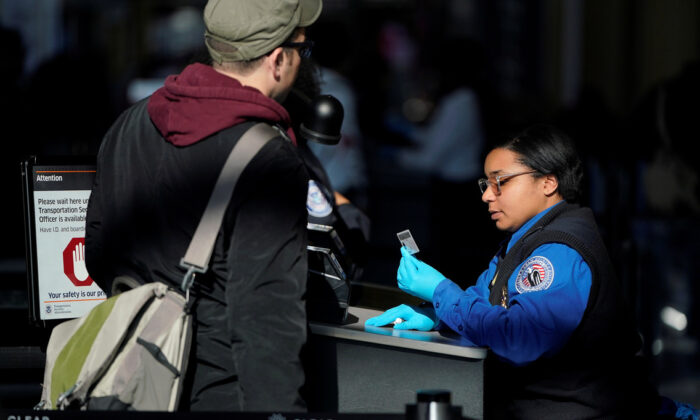 An employee with the Transportation Security Administration (TSA) checks the documents of a traveler at Reagan National Airport in Washington on Jan. 6, 2019. (Joshua Roberts/Reuters)