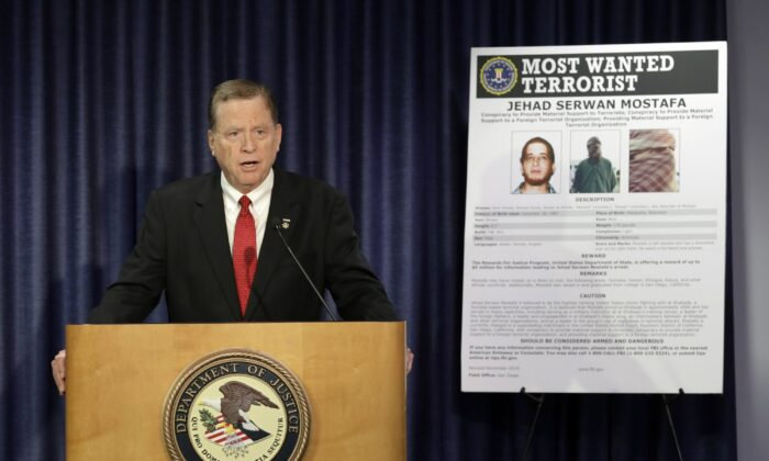 U.S Attorney Robert Brewer speaks in front of an FBI poster depicting Jehad Serwan Mostafa during a news conference in San Diego, California on Dec. 2, 2019. (Gregory Bull/AP Photo)