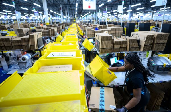 A woman works at a Amazon packing station