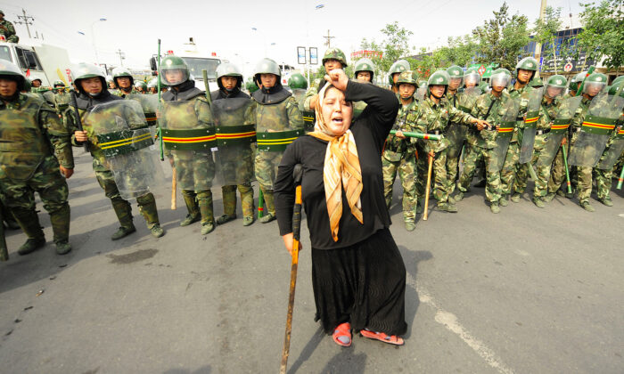 Chinese riot police watch a Muslim ethnic Uighur woman protest in Urumqi in China's far west Xinjiang province. (Getty Images | PETER PARKS)