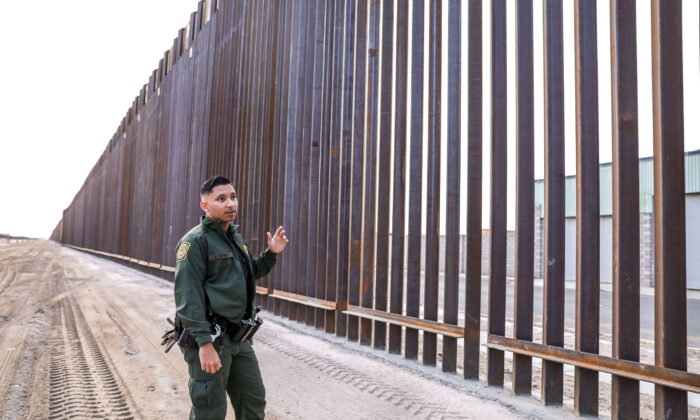 Border Patrol agent Jose Garibay stands next to part of the 30-foot high, 22-mile new fence on the U.S–Mexico border east of San Luis in Yuma, Ariz., on Nov. 27, 2019. (Charlotte Cuthbertson/The Epoch Times)