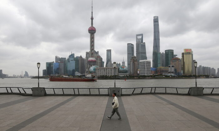 A man walks on the bund in front of the financial district of Pudong in Shanghai, China on March 9, 2016. (Aly Song/Reuters)