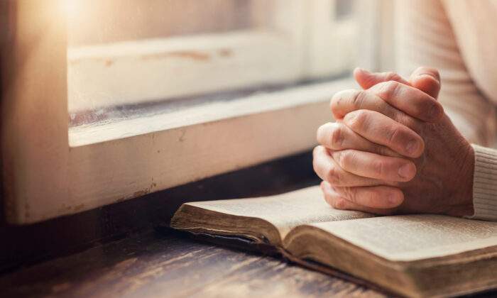 A person prays over a bible in a file photo. (Illustration/Shutterstock)
