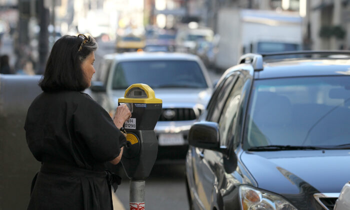A woman puts money into a parking meter in San Francisco, Calif., on Jan. 21, 2011. (Justin Sullivan/Getty Images)