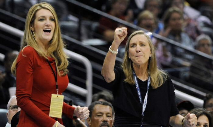 Mary Brock (R) and Kelly Loeffler cheer from their courtside seats as the Atlanta Dream basketball team plays in the second half of their WNBA basketball game, in Atlanta on Sept. 6, 2011. (David Tulis/AP Photo)