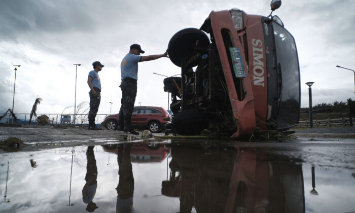 Police inspect a truck that was damaged as Typhoon Kammuri slammed Legazpi city, Albay province, southeast of Manila, Philippines, Dec. 3, 2019. (AP Photo)