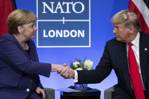 President Donald Trump shakes hands with German Chancellor Angela Merkel during the NATO summit at The Grove, Dec. 4, 2019, in Watford, England. (Evan Vucci/ AP Photo)