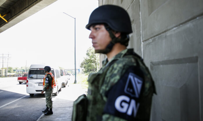 National Guard members provide security at a highway checkpoint for immigration authorities just south of Tapachula, Mexico, 25 miles north of the Suchiate River border with Guatemala, on June 28, 2019. (Charlotte Cuthbertson/The Epoch Times)