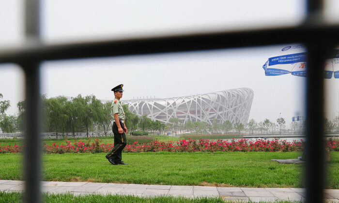 A paramilitary guard patrols the Olympic Green in front of the National Stadium in Beijing on July 2, 2008. (Frederic J. Brown/AFP via Getty Images)