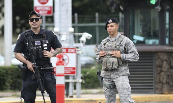 Security stand outside the main gate at Joint Base Pearl Harbor-Hickam in Honolulu on Dec. 4, 2019. (AP Photo/Caleb Jones)