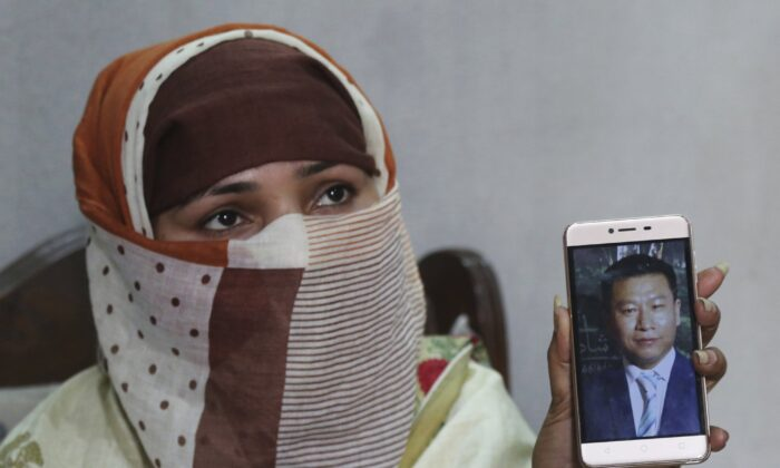 Sumaira a Pakistani woman, shows a picture of her Chinese husband in Gujranwala, Pakistan on May 22, 2019. Sumaira, who didn't want her full name used, was raped repeatedly by Chinese men at a house in Islamabad where she was brought to stay after her brothers arranged her marriage to the older Chinese man. (K.M. Chaudary/AP Photo)