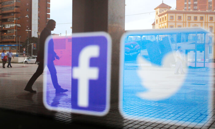 Facebook and Twitter logos are seen on a shop window in Malaga, Spain, June 4, 2018. (Reuters/Jon Nazca)