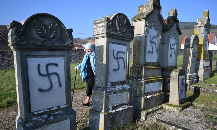 A woman walks by vandalized tombs at the jewish cemetery of Westhoffen near Strasbourg, eastern France on Dec. 4, 2019. (Patrick Hertzog/AFP via Getty Images)