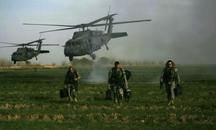 U.S. army special forces walk in a field as Blackhawk helicopters land on Feb. 24, 2010. Patrick Baz/AFP via Getty Images