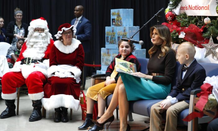 First Lady Melania Trump reads a Christmas book to children as she is seated between patients Sammie Burley (L) and Declan McCahan (R) at Children's National Hospital in Washington on Dec. 6, 2019. (Jacquelyn Martin/AP Photo)