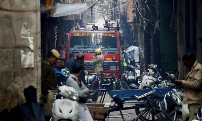 A fire engine stands by the site of a fire in an alleyway, tangled in electrical wire and too narrow for vehicles to access, in New Delhi, India, on Dec. 8, 2019. (Manish Swarup/AP Photo)