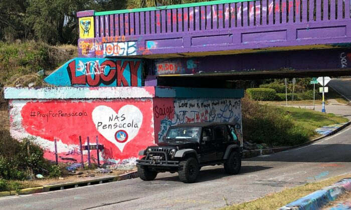 A vehicle drives by a tribute to victims of the Naval Air Station Pensacola that was freshly painted on what's known as Graffiti Bridge in downtown Pensacola, Fla., on Dec. 7, 2019.  (Brendan Farrington/AP Photo)