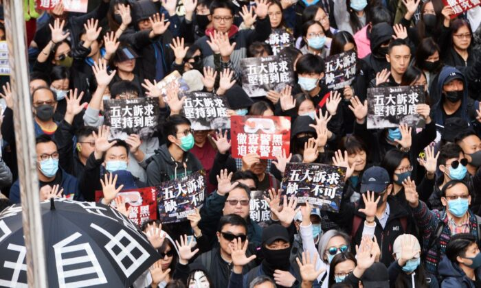Protesters hold up their hands in a sign of calling for their five demands in a march in Hong Kong on Dec. 8, 2019. (Sung Pi Lung/The Epoch Times)