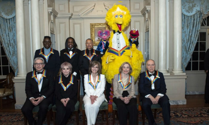 """Front row from left, 2019 Kennedy Center Honorees Michael Tilson Thomas, Linda Ronstadt, Sally Field, Joan Ganz Cooney, and Lloyd Morrisett. Back row from left, Philip Bailey, Verdine White, Ralph Johnson, and characters from """"Sesame Street,"""" Abby Cadabby, Big Bird, and Elmo in Washington, on Dec. 7, 2019. (Kevin Wolf/AP Photo)"""