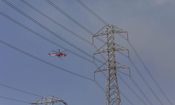 An air crane flies past PG&E power lines during firefighting operations in Healdsburg, Calif., on Oct. 26, 2019. (Philip Pacheco/AFP via Getty Images)