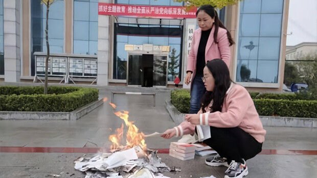 Two workers are seen burning books in front of the Zhenyuan county library in Qingyang City, Gansu Province, on Oct. 22, 2019. (Zhenyuan County official website)