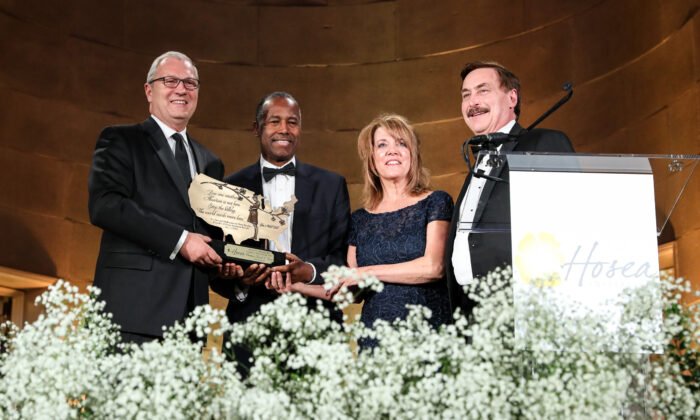 """Secretary of Housing and Urban Development Ben Carson (2nd L) receives the 2019 Dr. Bernard N. Nathanson """"Courageous Witness for Life Award"""" on behalf of President Donald Trump, next to Sen. Kevin Cramer (L) (R-N.D.), Terry Beatley, president of Hosea Initiative, and Michael Lindell, CEO of My Pillow, at The Life is Beautiful gala hosted by the Hosea Initiative at the Andrew W. Mellon Auditorium building in Washington on Dec. 9, 2019. (Samira Bouaou/The Epoch Times)"""