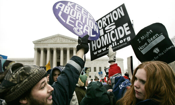 """Pro-life activist Jessica Meunier (R) of Fitchburg, MA, and pro-abortion activist Luqman Clark (L) of Arlington, VA hold up signs as they protest outside U.S. Supreme Court during the """"March for Life"""" event January 24, 2005 in Washington, DC.   Alex Wong/Getty Images"""