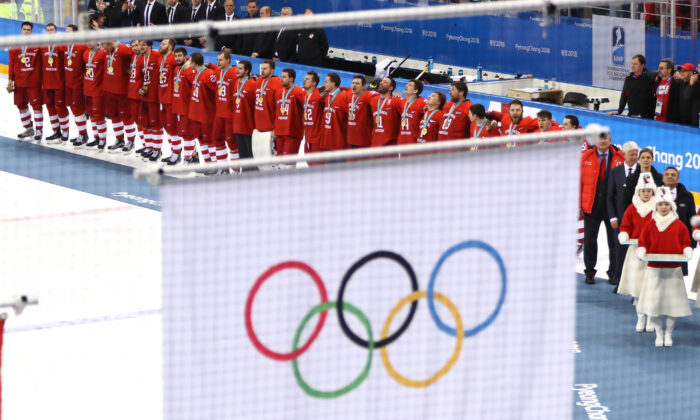 Gold medal winners Olympic Athletes from Russia look on as the Olympic flag is raised during the medal ceremony after the Men's Gold Medal Game against Germany on day sixteen of the PyeongChang 2018 Winter Olympic Games at Gangneung Hockey Centre in Gangneung, South Korea on Feb. 25, 2018. (Jamie Squire/Getty Images)