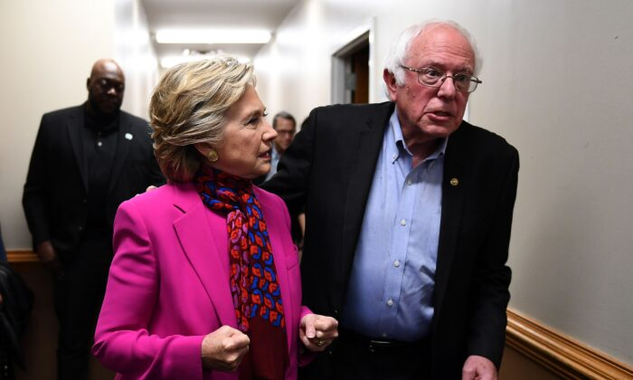Democratic presidential nominee Hillary Clinton talks with Sen. Bernie Sanders (I-Vt.) backstage before a campaign rally in Raleigh, N.C., on Nov. 3, 2016. (Jewel Samad/AFP via Getty Images)