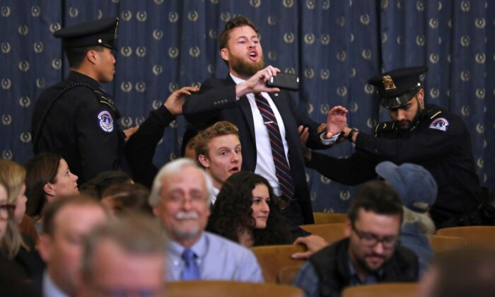 Infowars host Owen Shroyer shouts as he is removed by police after interrupting a House Judiciary Committee hearing on impeachment in the Longworth House Office Building on Capitol Hill in Washington on Dec. 9, 2019. (Chip Somodevilla/Getty Images)