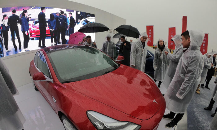 Guests look at a Tesla Model 3 during a ground-breaking ceremony for a Tesla factory in Shanghai, China on Jan. 7, 2019. (STR/AFP via Getty Images)
